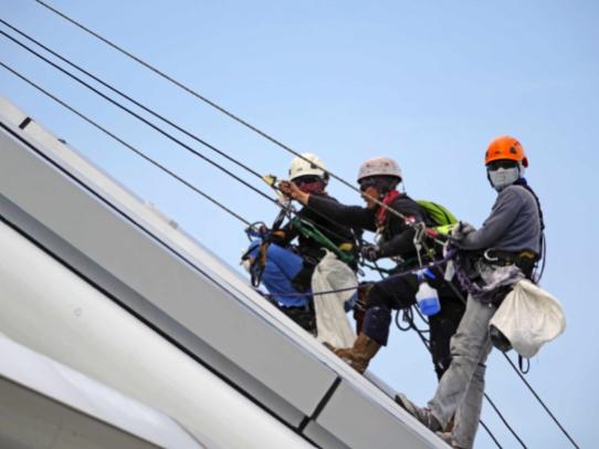 Three men safely conducting roof maintenance